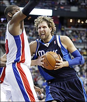 Dirk Nowitzki of Dallas drives against Detroit's Greg Monroe.