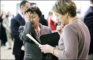 Ann Oganesian, left, of Newton, Mass., speaks with a State Department employee about job opportunities during a job fair in Boston. U.S. employers ramped up hiring in February, adding 236,000 jobs.