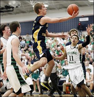 Toledo Christian's Eric Cellier, who had 13 points, goes to the basket against Ottawa Hills' A.J. King (11).