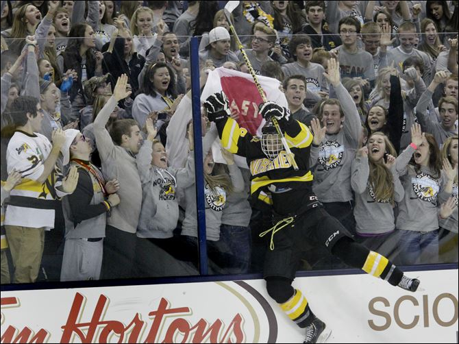 Northview's senior Xavier Sudlow jumps against the glass to cheering Wildcat fans after the win.