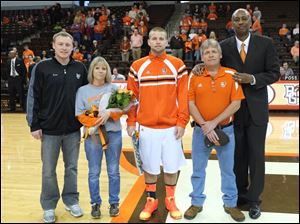 Bowling Green senior basketball player Luke Kraus, center, with his brother Zack, left, mother Cindy, father Dave, and coach Loius Orr, is honored.