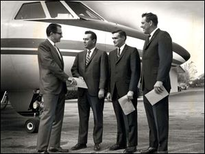 Dana Corp pilots stand by the company plane.