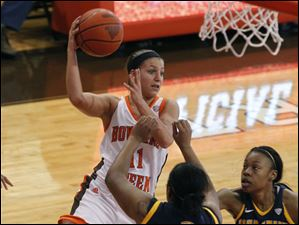 BGSU's Jillian Halfhill passes over Kent State's Diamon Beckford (11) and Ashley Evans.