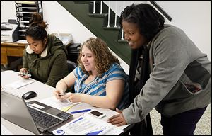 Financial coach Wendy Easler, right, and Nadine Bryant, center, of the United Way help Disarea Segura of Toledo with her taxes at the Financial Opportunity Center in North Toledo.