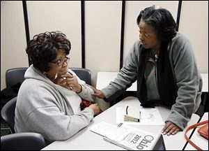 Wendy Easler, right, helps Deborah Foreman of Toledo with her taxes Friday at the Financial Opportunity Center in North Toledo.