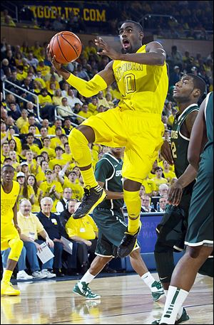 Michigan's Tim Hardaway, Jr., leaps past Michigan State's Branden Dawson, right, for a basket. UM has unlikely fans as OSU will root for them to beat Indiana.