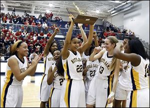 Notre Dame's Jayda Worthy lifts the trophy the Eagles received after winning the regional championship. Worthy had a big hand in the victory, sinking the clinching free throws in the final seconds.