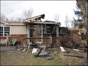 This photo shows the charred remains of  a home after a fire erupted, Saturday, in Gray, Ky.