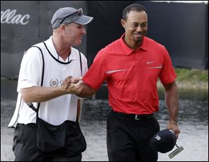 Tiger Woods, right, and his caddie Joe Lacava congratulate each other after winning the Cadillac Championship. Woods shot a 1-under-71 on Sunday to win.