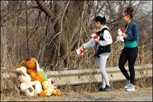 Dominique Ellison, left, and Rickie Bowling of Warren bring stuffed animals to a memorial in honor of their friends who died in a car crash Sunday on Park Avenue in Warren, Ohio.