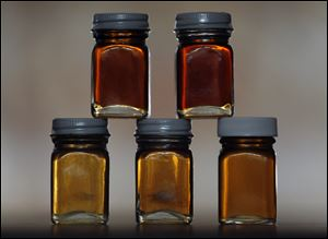 "Various grades of maple syrup are displayed. Gov. Rick Snyder has declared March ""Michigan Maple Syrup Month"" in honor of the industry's contribution to the state economy."