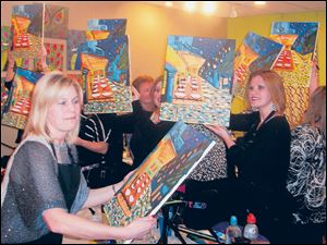 Jennifer Kranz, left, and other students hold their finished paintings.