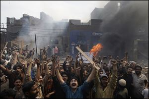 An angry mob reacts after burning Christian houses in Lahore, Pakistan, Saturday.