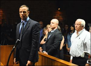Olympian Oscar Pistorius stands following his bail hearing in Pretoria, South Africa, last month.
