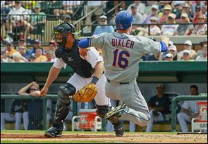 The Mets' Brian Bixler scores in the fifth inning before Tigers catcher Bryan Holaday can get the throw. Bixler also homered for New York.