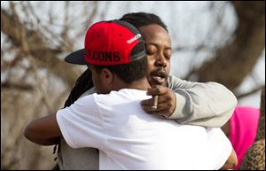 Leaman Joe, left, hugs Michael Parker, at the crash site that killed their friends on Park Ave. in Warren, Ohio, Sunday.