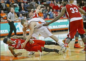 The game gets physical as Miami's Geovonie McKnight is knocked over by BG's Luke Kraus during second half of the first round of the MAC tournament at the Stroh Center on Monday.