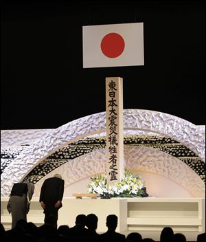Japanese Emperor Akihito, right, and Empress Michiko bow to pay tribute to the victims of the March 11 earthquake and tsunami at the national memorial service in Tokyo.