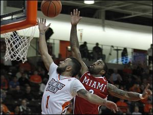 BGSU's Jordon Crawford gets his shot blocked from behind by Miami's Quinten Rollins during the first round of the MAC tournament.