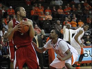 Miami's Allen Roberts protects the ball from BGSU's Chauncey Orr after rebounding a missed BGSU basket.