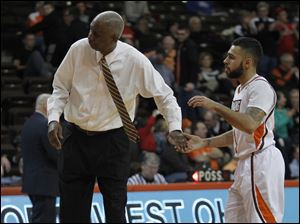 BGSU head coach Louis Orr shakes hands with Jordon Crawford after Crawford scored against Miami.