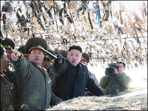North Korean leader Kim Jong Un, third left, looks at South's western border island of Baengnyeong during his visit to the Wolnae Islet Defense Detachment, North Korea, Monday.