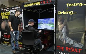 Owens student Alex Bohland texts and drives in the simulator, as  Adam Kelly, an employee of the firm which tours the simulator, watches.