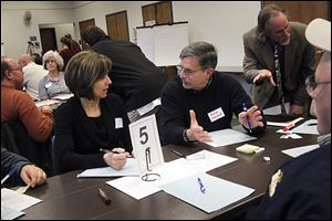 Robin Whitney, left, Toledo's public utilities commissioner of engineering services, talks with John Clement of West Toledo during the first public forum to review street planning and address residents' questions and concerns. They met at the Sanger branch of the Toledo-Lucas County Public Library.