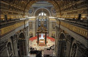 Cardinals, in red, and other prelates and faithful attend a Mass for the election of a new pope celebrated by Cardinal Angelo Sodano, inside St. Peter's Basilica, at the Vatican.