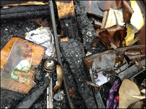 A partially burned child's photo is seen Monday in the debris of a house fire in which seven people were killed Saturday in southeastern Kentucky. Officials say two adults and five children were killed in the fire in Gray, Ky.