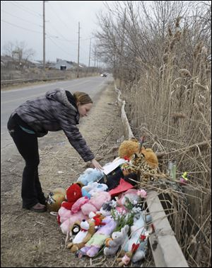 Shannon Whetstone reads notes Monday at the scene where six teens died in a crash early Sunday in Warren, Ohio. Two teenagers survived the crash.