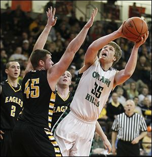 Ottawa Hills' Lucas Janowicz puts up a shot against Colonel Crawford's Clay Jury (45) during a Division IV regional semifinal at Bowling Green State University. Janowicz scored 10 points.