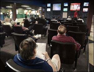 Fans watch races from Toledo and other tracks on monitors at Raceway Park, which will close next year to ease competition for the casino in East Toledo.