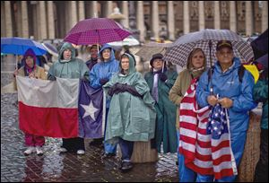A group waiting in St. Peter's Square holds U.S. and Texas flags while watching a video monitor during the first day of voting for a new pope.