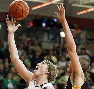 RJ Coil takes a shot against Colonel Crawford's Nate Klingenberger. Coil scored 14 to lead Ottawa Hills.
