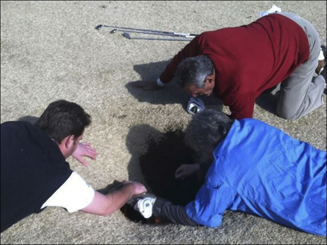 Golfer Illinois Sinkhole Hank Martinez, top, Ed Magaletta, right, and Russ Nobbe, look into an 18-foot-deep and 10-foot- wide sinkhole that golfer Mark Minhal fell into while playing golf at the Annbriar Golf Course in Waterloo, Ill.