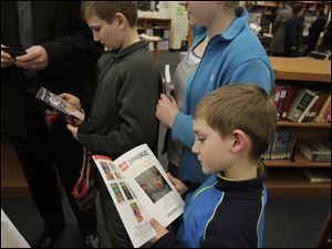 Jonathan Doenecke, 7, center, took a look at his new book as he and his siblings browsed through the book fair.
