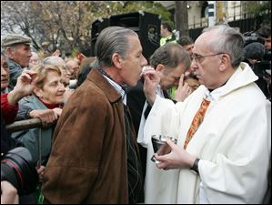 cardinal Jorge Bergoglio, right, gives the holy communion to Argentina's former army chief  Roberto Bendini in 2009 in Buenos Aires, Argentina.