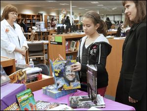 Victoria, 12, center, and Kathie Hagmeyer, of Sylvania, right, browse through the selection at the book fair.