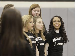 Kenni Green, 13, right, smiled as she and her fellow eighth grade choir members performed.