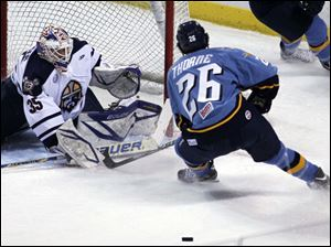 Greenville goalie Scott Stajcer deflects a puck from Walleye Stephon Thorne.