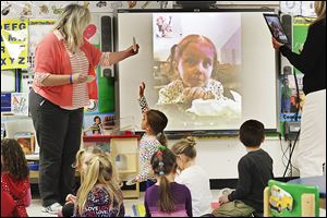 Preschool teacher Lori Brown, left, poses a question to Kyra Conrad, 4, who was using FaceTime to interact with her classmates Wednesday afternoon at Danbury Elementary in Marblehead. For two hours each day, Kyra uses an iPad to FaceTime with her class.