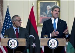 Secretary of State John Kerry, accompanied by Libyan Prime Minister Ali Zeidan gestures as he speaks to reporters during their joint news conference at the State Department in Washington today.