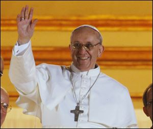 Pope Francis waves to the crowd from the central balcony of St. Peter's Basilica today at the Vatican.