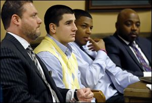 From left, Defense attorney Adam Nemann, his client, defendant Trent Mays, 17, defendant 16-year-old Ma'lik Richmond and his attorney, Walter Madison, listen to testimony during Mays and Richmond's trial on rape charges in juvenile court in Steubenville, Ohio.