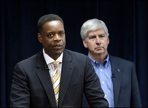Kevyn Orr, left, speaks as as Michigan  Gov. Rick Snyder listens during a news conference in Detroit.