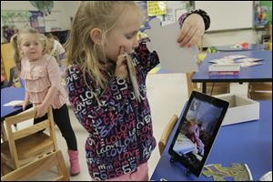 Jessica Baxter, 5, center, shows Kyra Conrad, on the screen at right, the puzzle pieces as she puts them together during class Wednesday afternoon.