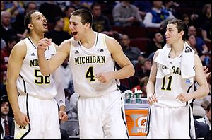 From left, Michigan's Jordan Morgan, Mitch McGary, and Nik Stauskas celebrate Thursday during their Big Ten tournament win against Penn State.
