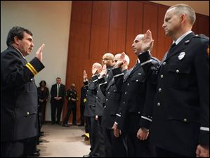 David Dauer Toledo Fire and Rescue Department CFO and battalion chief, left, swears in newly promoted captains.