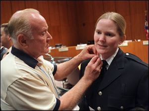 James McConkey pins lieutenant's collar brass on the shirt of his daughter Kathy Zeller after she was promoted from private to lieutenant.